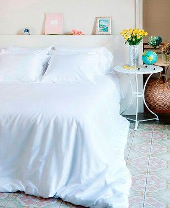 habitación con sábanas blancas y funda nórdica