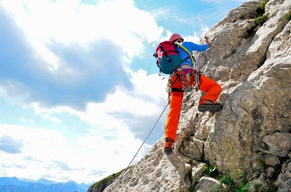 deportista subiendo una roca con pantalón de escalada de hombre naranja